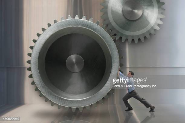 Mixed race businessman turning large metal gears