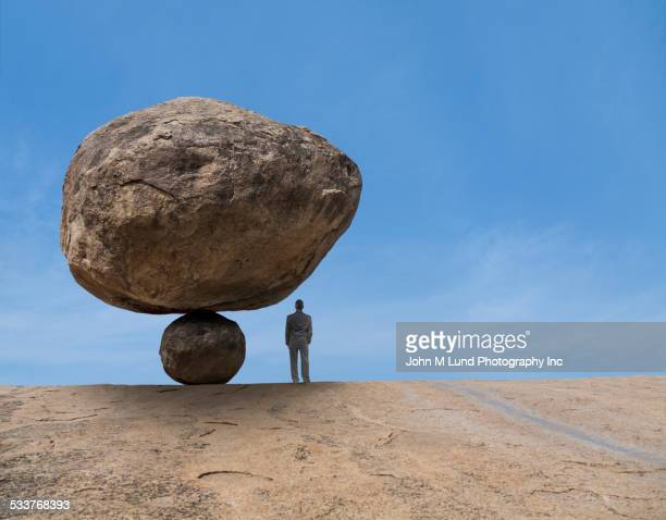 Mixed race businessman under risky balancing boulder