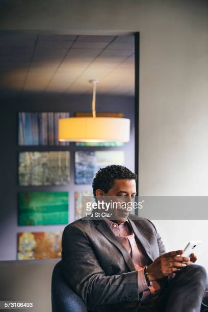 Mixed race businessman using cell phone in office lobby