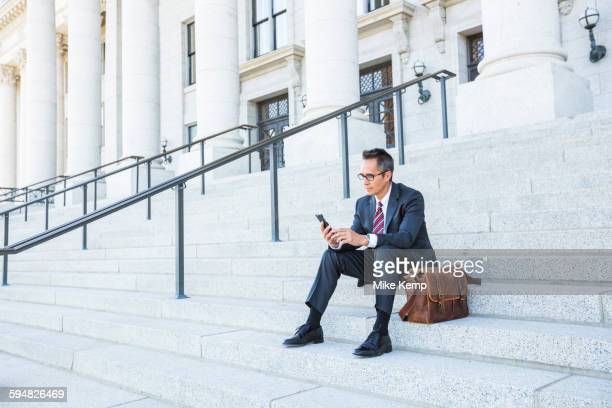 Mixed race businessman using cell phone on courthouse steps