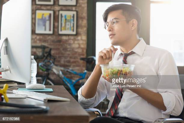 mixed race businessman using computer and eating salad at desk - 昼食 ストックフォトと画像