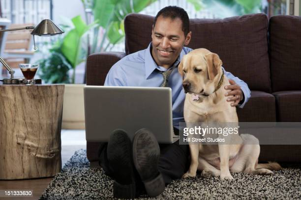 Mixed race businessman using digital tablet and petting dog
