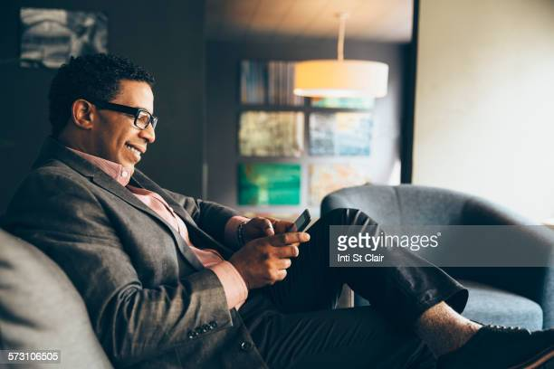 Mixed race businessman using digital tablet in office lobby