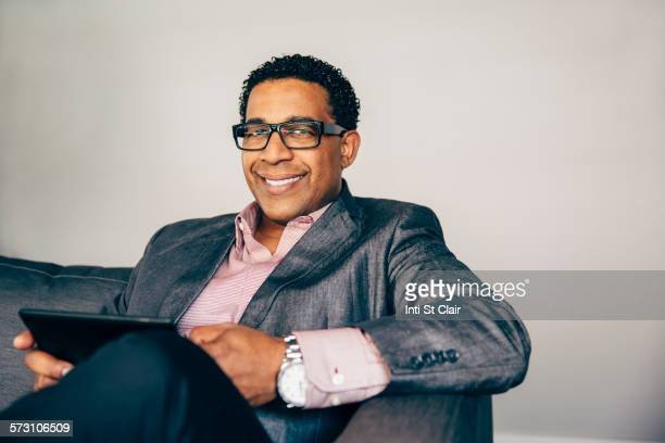 Mixed race businessman using digital tablet on sofa