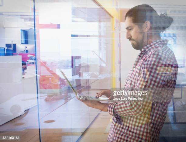Mixed Race businessman using laptop behind glass wall
