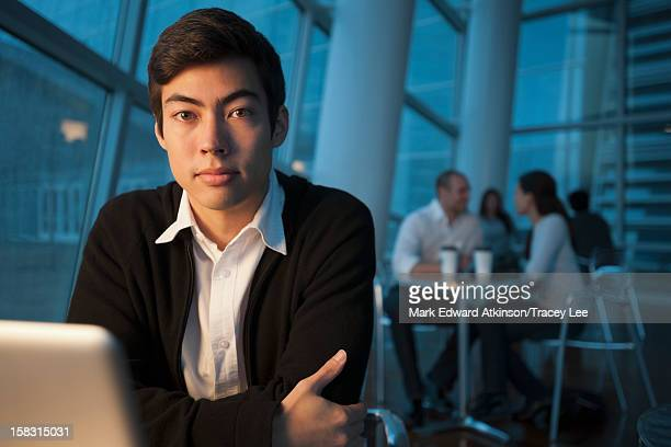 Mixed race businessman using laptop in cafe
