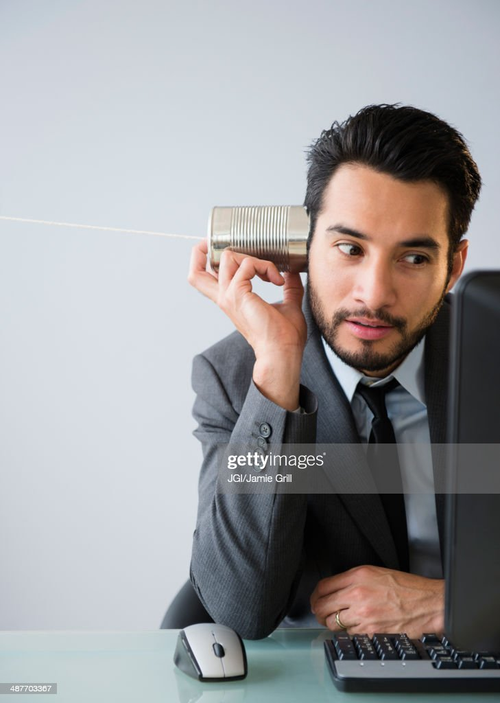 Mixed race businessman using tin can telephone : Stock Photo