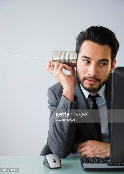 Mixed race businessman using tin can telephone