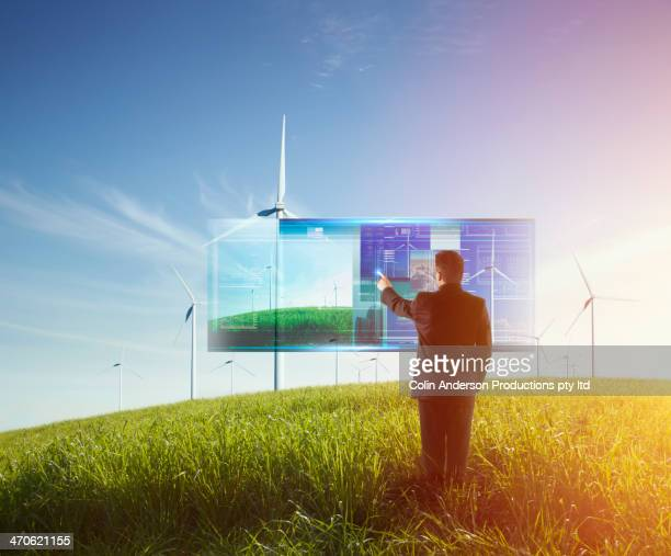Mixed race businessman using touch screen computer outdoors