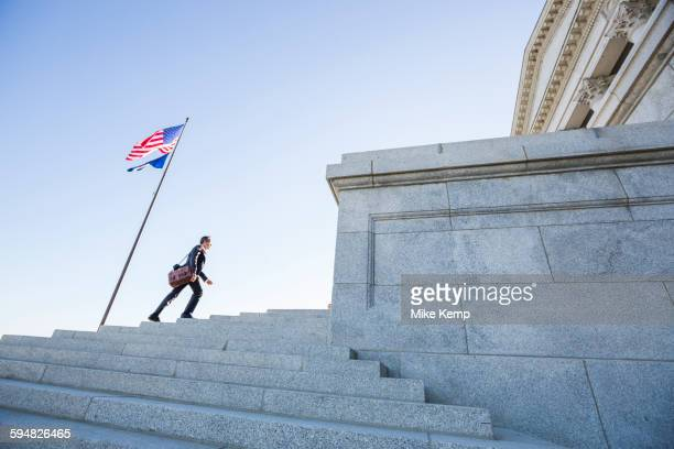 Mixed race businessman walking on courthouse steps
