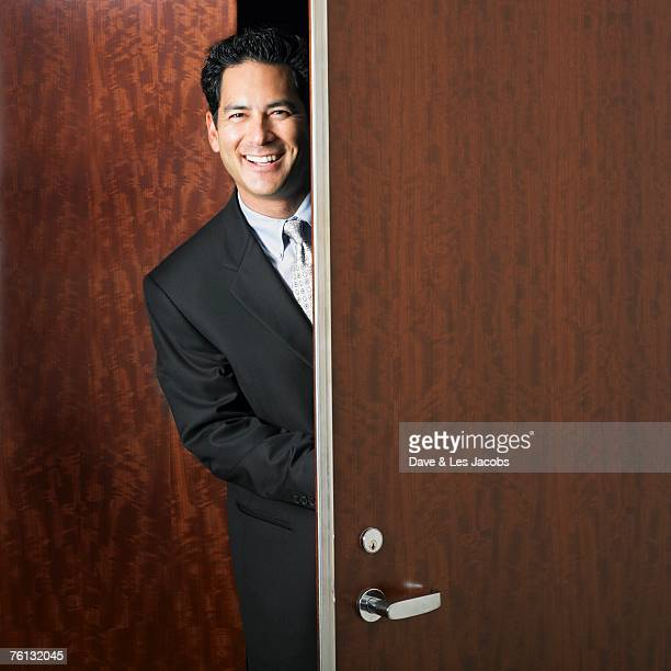Mixed Race businessman walking through doorway