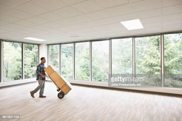 mixed race businessman wheeling boxes in empty office - empurrar atividade física imagens e fotografias de stock