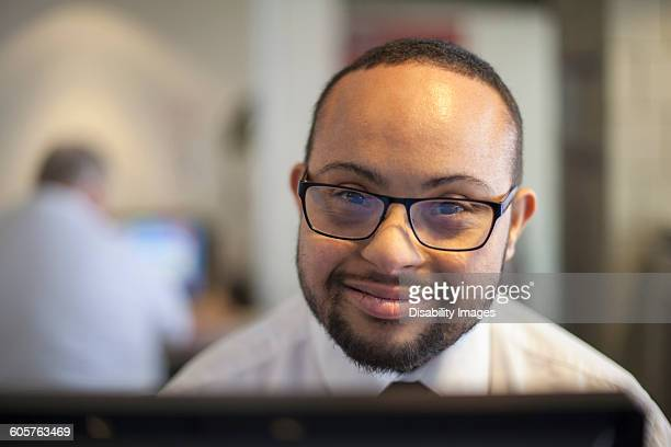 Mixed race businessman with down syndrome working on computer
