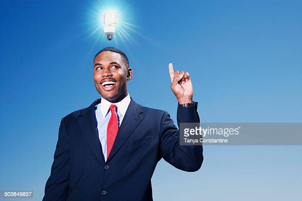 Mixed race businessman with light bulb over his head