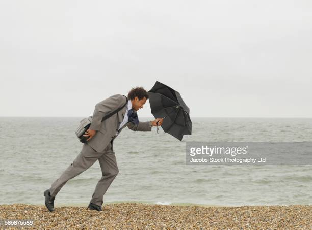 Mixed race businessman with umbrella walking on windy beach