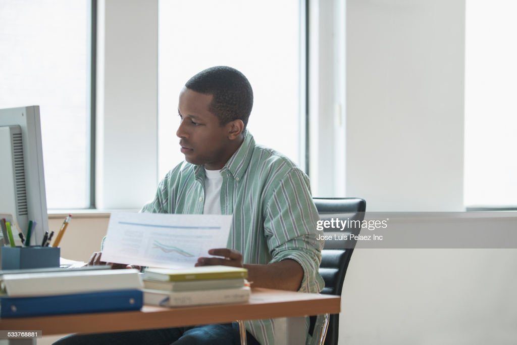 Mixed race businessman working at desk : Foto stock