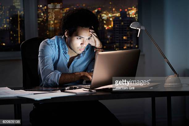 Mixed race businessman working late in office