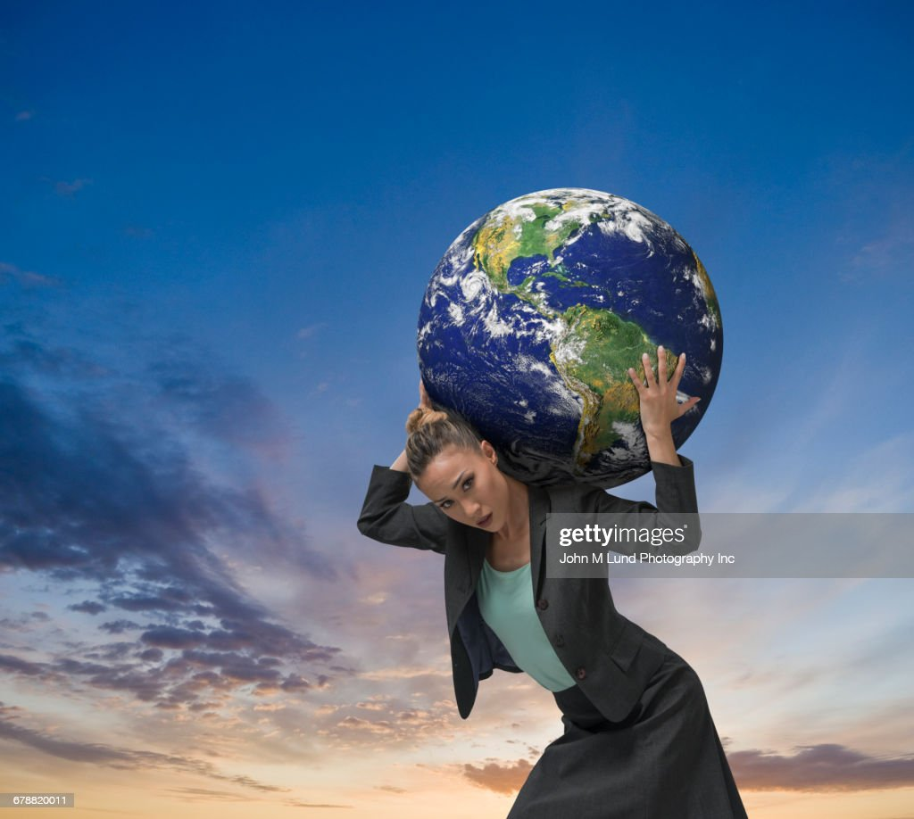 mixed race businesswoman carrying earth on shoulders stock photo