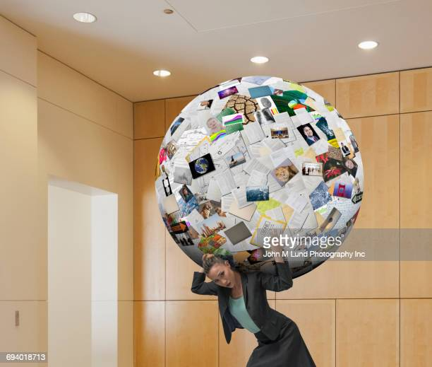 Mixed Race businesswoman carrying heavy social media globe