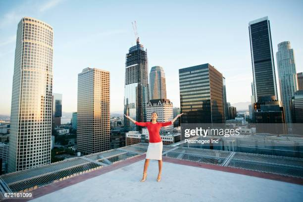 Mixed Race businesswoman celebrating on urban rooftop