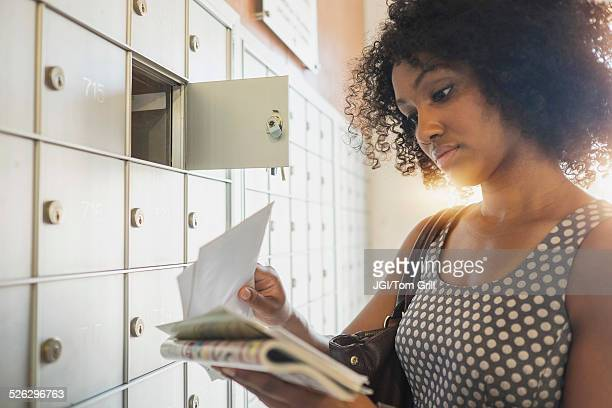 mixed race businesswoman checking mailbox - mail stock pictures, royalty-free photos & images