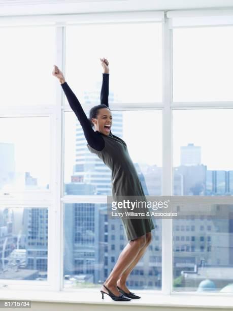 Mixed Race businesswoman cheering