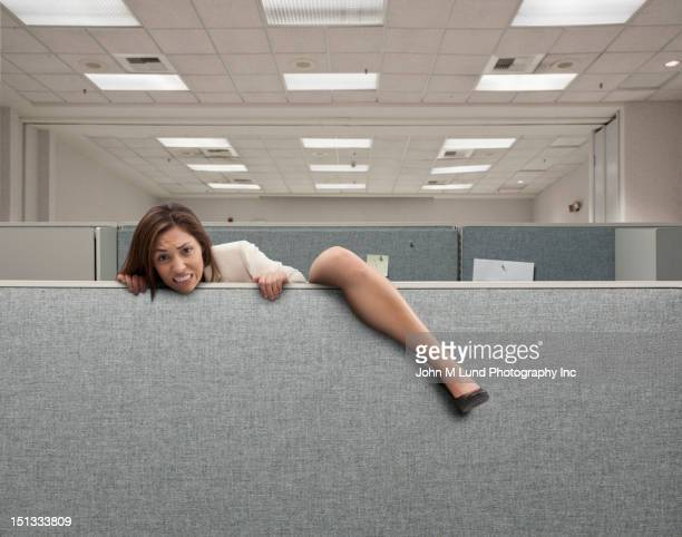 Mixed race businesswoman climbing over cubicle wall