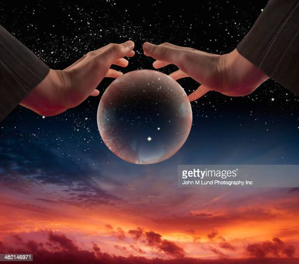 mixed race businesswoman cupping planet in sky - domination stock pictures, royalty-free photos & images