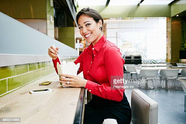 Mixed Race businesswoman eating food with chopsticks in food court
