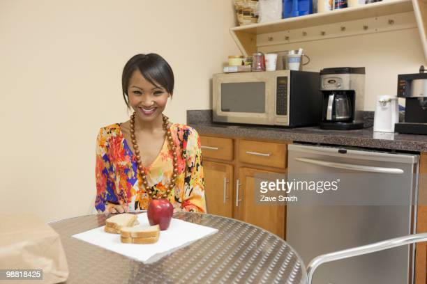Mixed race businesswoman eating lunch in break room
