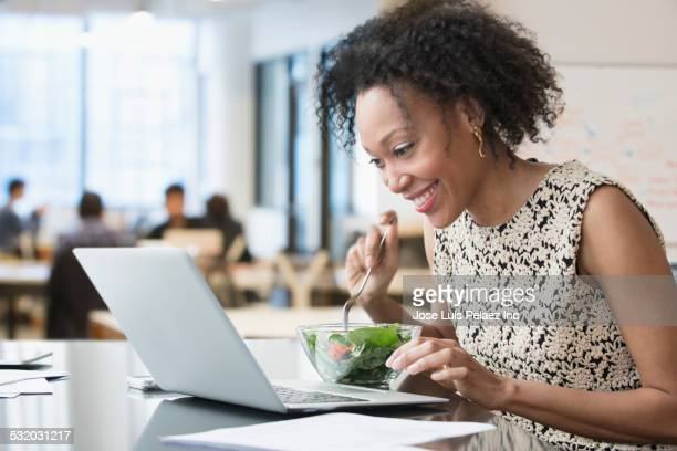 Mixed race businesswoman eating salad at desk in office