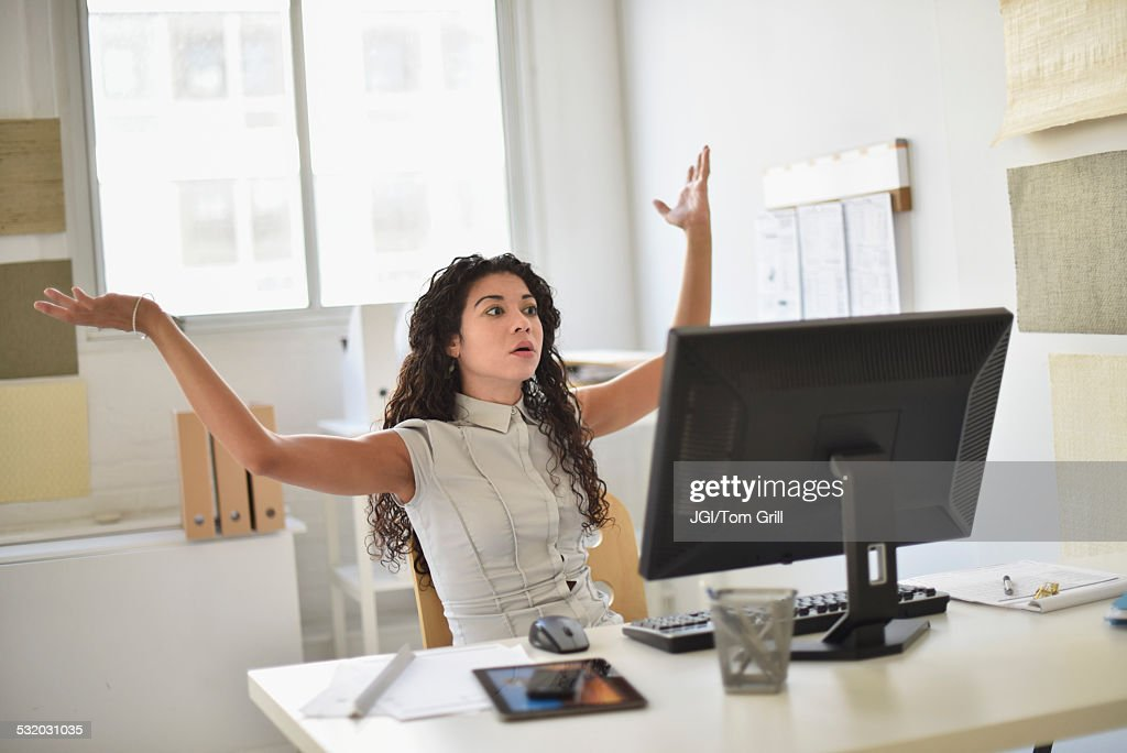 Mixed race businesswoman frustrated at computer at desk in office : Stock Photo