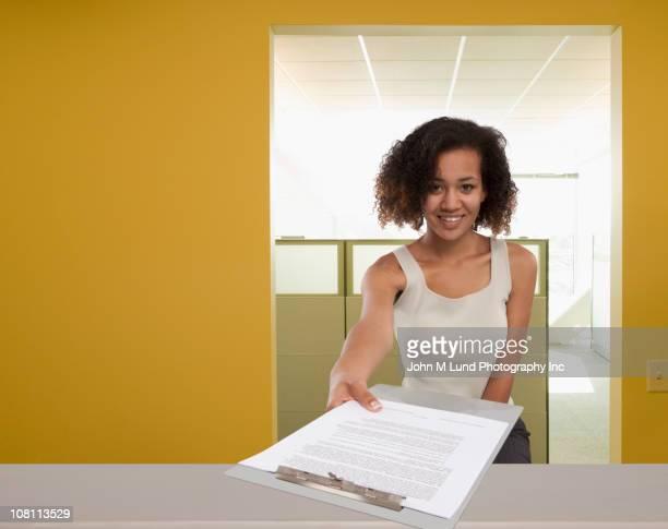 Mixed race businesswoman handing over clipboard