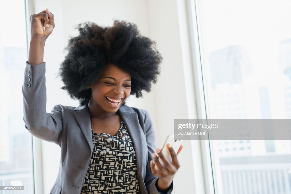 Mixed race businesswoman holding cell phone and cheering : Stock Photo