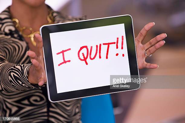 mixed race businesswoman holding tablet computer that reads 'i quit!! - quitting a job stock pictures, royalty-free photos & images