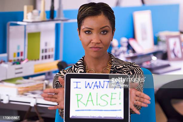 Mixed race businesswoman holding tablet computer that reads 'I want a raise!