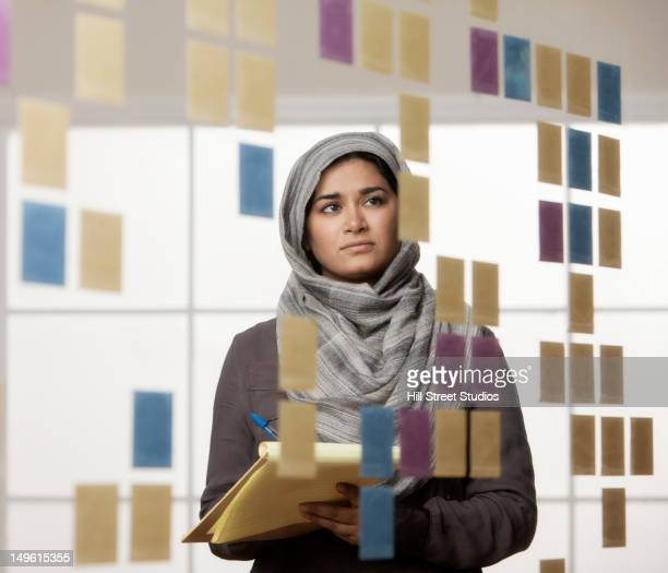Mixed race businesswoman in hijab looking at sticky notes in office