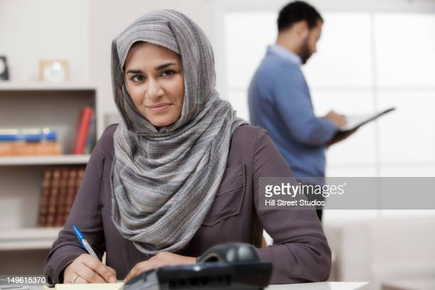 Mixed race businesswoman in hijab working at desk
