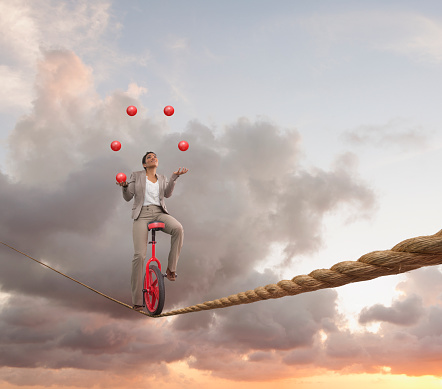 Mixed race businesswoman juggling on tightrope on unicycle - gettyimageskorea