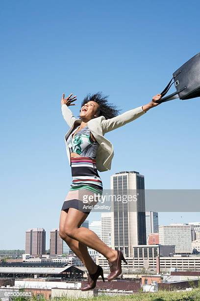 Mixed Race businesswoman jumping for joy in city