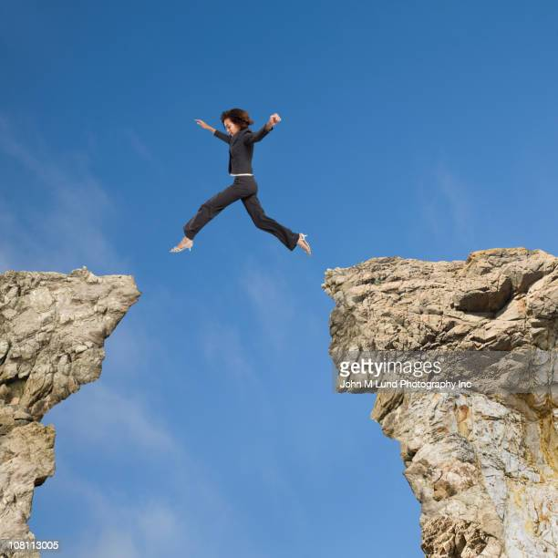 Mixed race businesswoman jumping over gap between cliffs