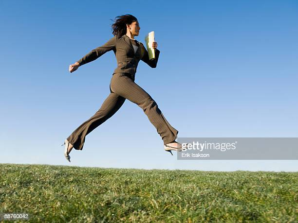 Mixed race businesswoman leaping in field