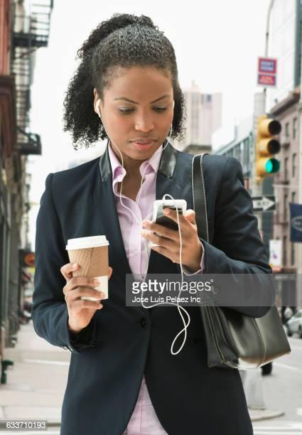 Mixed race businesswoman listening to earphones