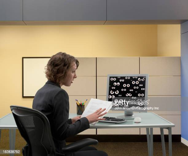 Mixed race businesswoman looking at eyes peering from monitor