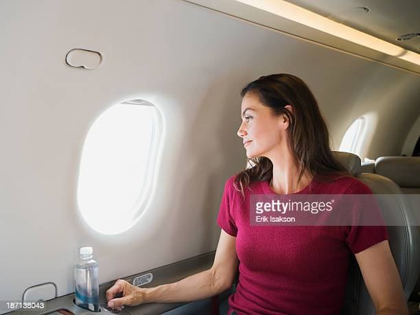 Mixed race businesswoman looking out airplane window