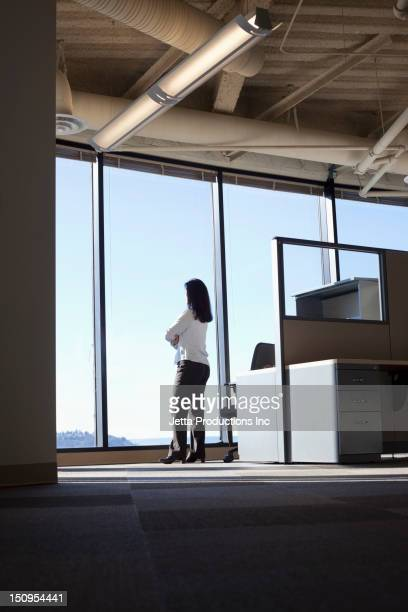Mixed race businesswoman looking out office window