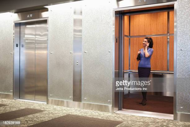 Mixed race businesswoman on cell phone in elevator