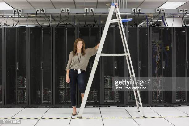 Mixed race businesswoman on ladder in server room