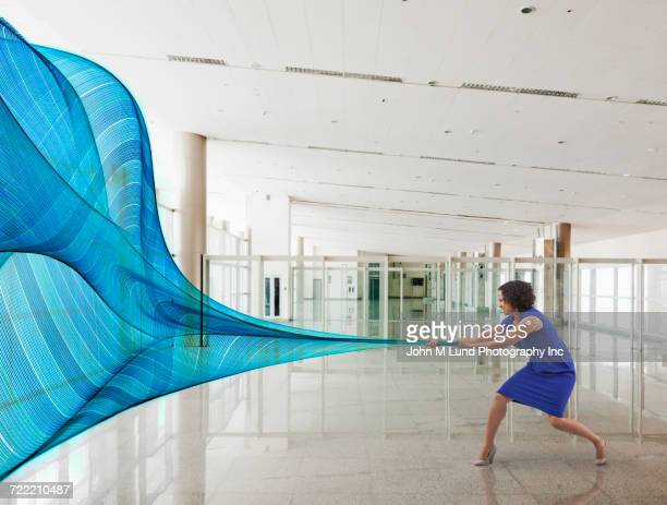 mixed race businesswoman pulling blue data waves - waving gesture stock photos and pictures