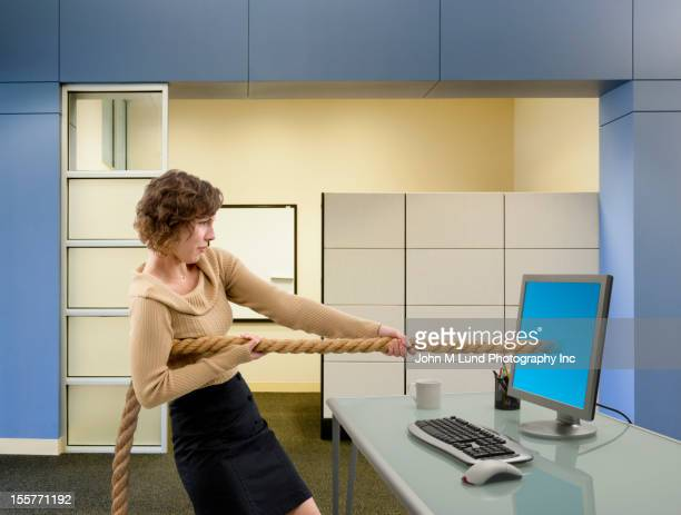 Mixed race businesswoman pulling rope from computer monitor